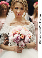 b5b9295410c7e Smiling blonde bride in pearl necklace holding orange rose in the ...