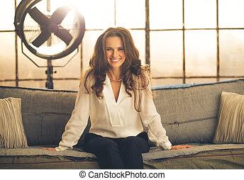 Smiling, elegant woman leaning forward sitting on sofa in...