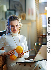 smiling elegant woman with yarn learn how to knit