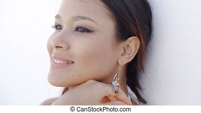 Smiling elegant young woman wearing drop earrings looking into the distance with a dreamy expression close up of her face in a beauty concept