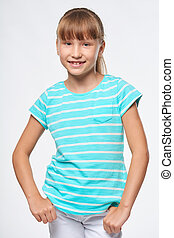 Smiling elementary school age girl standing relaxed with ...