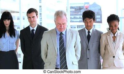 Smiling employees standing upright together
