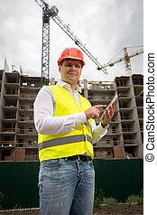 Smiling engineer using digital tablet at building site