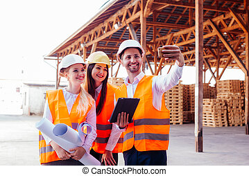 Smiling engineers taking selfie at contruction site. Successful teamwork concept