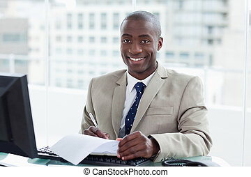 Smiling entrepreneur signing a document in his office