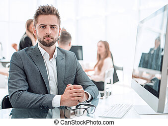 smiling entrepreneur sitting at an office Desk