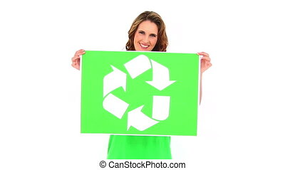 Smiling environmental activist showing poster on white...