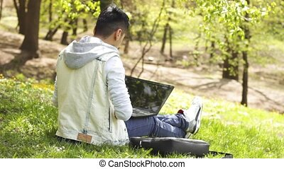 Smiling ethnic man using laptop in park - Cheerful young man...