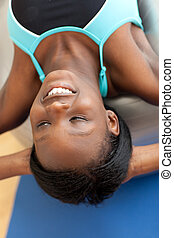 Smiling ethnic woman working out with a pilates ball