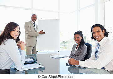 Smiling executive showing a flipchart with his relaxed colleagues