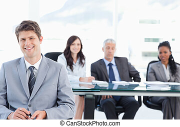 Smiling executive sitting in front of his earnest team and looking at the camera