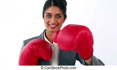 Smiling executive using red boxing gloves