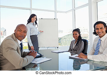 Smiling executive woman giving a presentation to her relaxed coworkers
