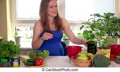 Smiling expectant mother making salad from fresh organic vegetables