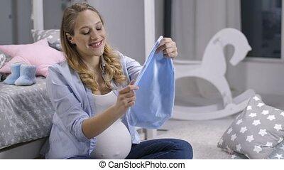 Smiling expecting woman holding newborn onesie - Beautiful...