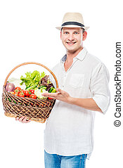 Smiling experienced farmer with a harvest of vegetables on a white background