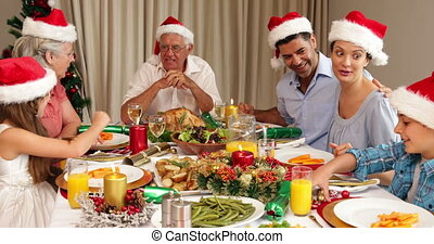 Smiling extended family at christmas dinner - Smiling...