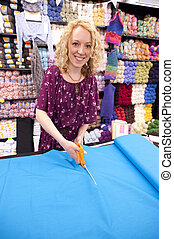 smiling fabric store girl - girl cutting fabric in a fabric...