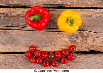 Smiling face with bell peppers for eyes, and stem of tomatoes.