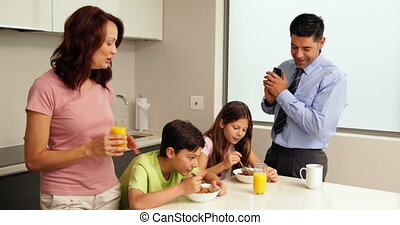 Smiling family at breakfast before father goes to work at...