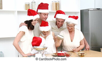 Smiling family baking Christmas cakes