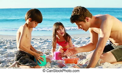 Smiling family building sand castles on the beach