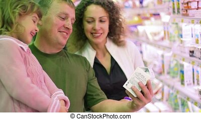 smiling family buying yogurt in supermarket