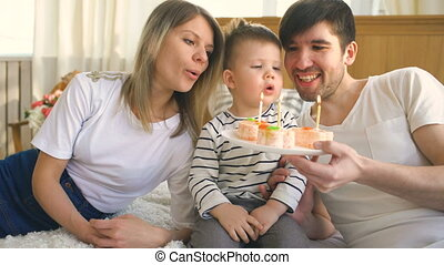 Smiling family celebrating their son birthday together and blowing candles on cake