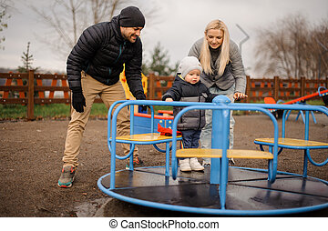 Smiling family couple with little son riding on the carousel