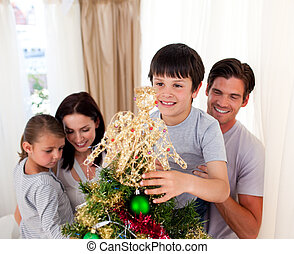 Smiling family decorating a Christmas tree at home
