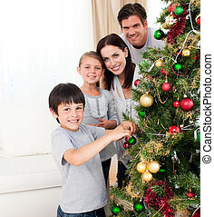 Smiling family decorating a Christmas tree in the...
