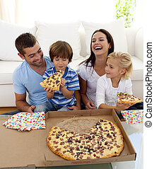 Smiling family eating pizza in living-room all together - ...