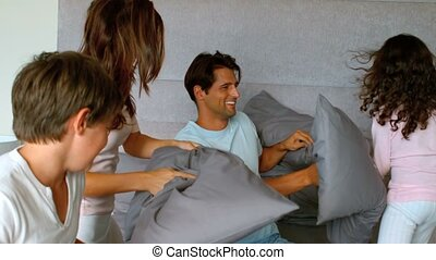 Smiling family having a pillow figh