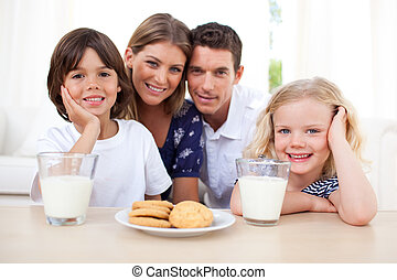 Smiling family having breakfast at