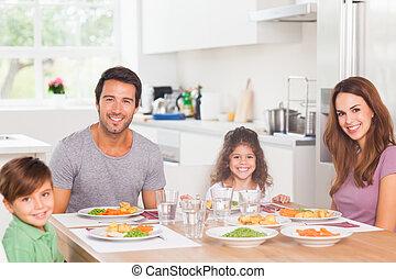 Smiling family having dinner in kitchen
