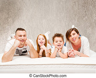 Smiling family having fun lying on the bed