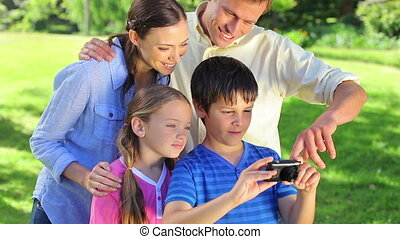 Smiling family helping a little boy with his camera