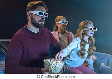Smiling family in 3d glasses watching movie and eating popcorn