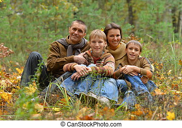 Smiling family in autumn forest sitting