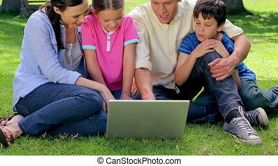 Smiling family looking at a laptop together