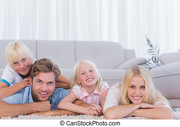 Smiling family lying on the carpet