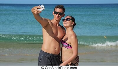 smiling family makes selfie on sunny beach near azure ocean...