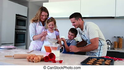 Smiling family making a cake togeth