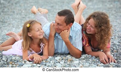 smiling family of three persons lying on pebble beach and talking