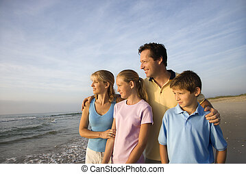 Portrait of Caucasian family of four posing on beach looking at ocean.