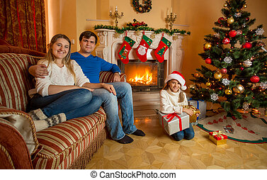 Smiling family posing at living room decorated for Christmas with burning fireplace