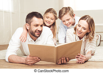 smiling family reading book while lying on the floor at home together