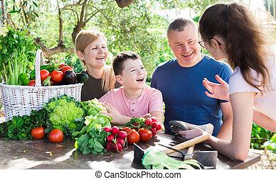 Smiling family spending time at table in backyard garden