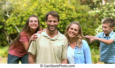 Smiling family spending time together in a park in slow...