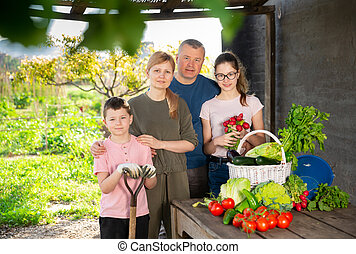 Smiling family standing on backyard with harvested ...